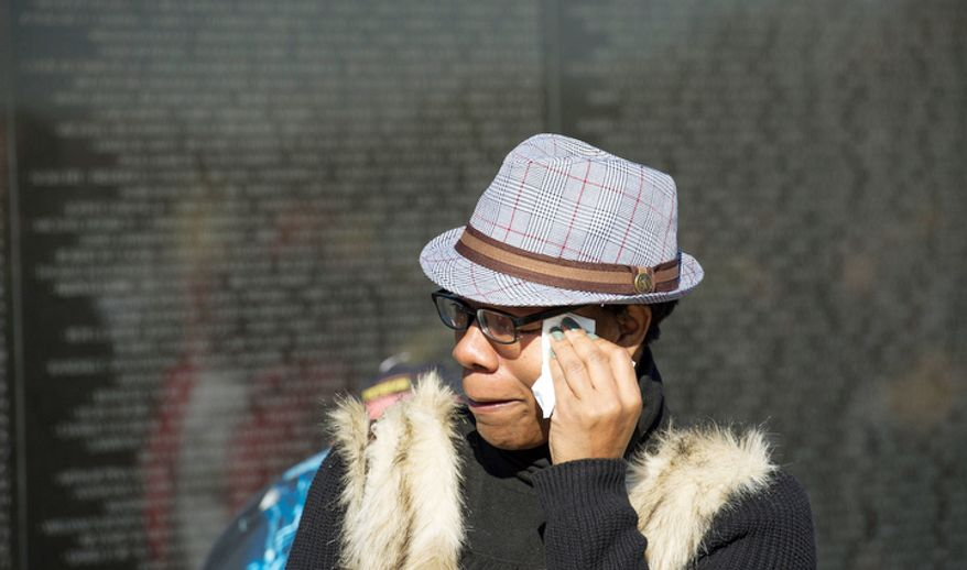 Valencia Adams, of Bowie, Md., wipes tears from her eyes after getting a pencil rubbing of the name of her father Army Pvt. Phillip C. Adams who was killed in Vietnam on May 5, 1970 after being in country for 6 months, as she visits the wall at the Vietnam Veterans Memorial during Veteran's Day weekend in Washington, D.C. Her son is retiring soon from the military after tours in Afghanistan and Iraq. (Rod Lamkey Jr./The Washington Times)