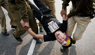 Indian police detain a Tibetan Youth Congress supporter protesting outside the Chinese Embassy in New Delhi on Monday. China has blamed the Dalai Lama for the glorification of a wave of self-immolations among Tibetans. (Associated Press)