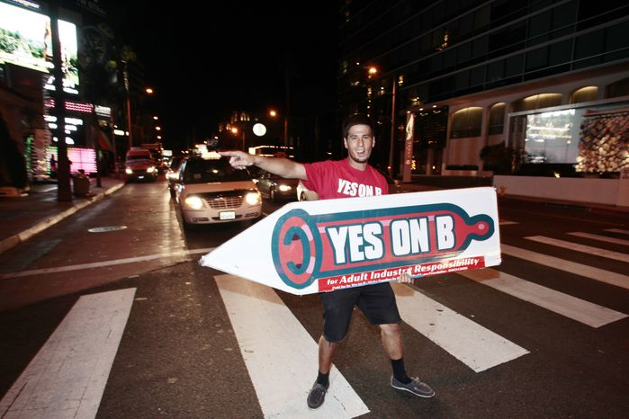 "**FILE** Supporters of ""Vote Yes on B in Los Angeles,"" the condom-use-in-porn measure on the November ballot led by AIDS Healthcare Foundation, hand out voter information and free condoms on Los Angeles' famed Sunset Strip on Oct. 27, 2012. (Joe Kohen/AIDS Healthcare Foundation via Associated Press)"