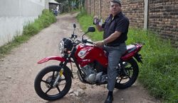 Wilfredo Yanes sits on his motorcycle Oct. 17, 2012, shows pictures of his late son Ebed Jaasiel Yanes, 15, at the site where he was shot dead, allegedly by soldiers in Tegucigalpa, Honduras. According to his relatives, Yanes was killed by soldiers early May 27, when he was riding a motorcycle near a military checkpoint. (Associated Press)