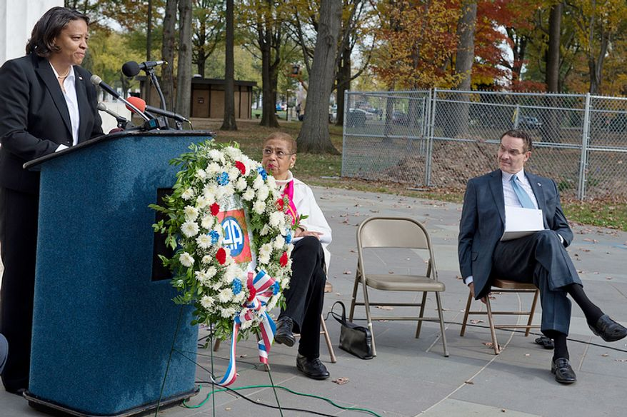 Congresswoman Eleanor Holmes-Norton, center, and Mayor Vincent Gray look on as Tomi Rucker, a Washington, D.C. Navy mom, talks about how she and her husband were saddened by the fact that the D.C. flag was not a part of her son's Navy boot camp graduation, when flags from the other states with graduates were present. Ms. Rucker joined the D.C. officials at the D.C. World War I Memorial on Monday, Nov. 12, 2012 to talk about the inconsistent flying of the D.C. flag at military graduations. (Barbara L. Salisbury/The Washington Times)