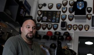 Extreme far-right Golden Dawn party lawmaker Ilias Panagiotaros speaks Oct. 26, 2012, at his shop in central Athens, explaining his party's policies and rejects accusations that it has been involved in racist attacks in Greece. (Associated Press)