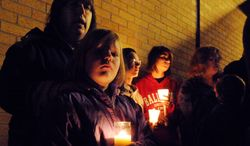 Ahna McCue and her daughter, Emily, attend a candlelight vigil on Nov. 11, 2012, at Southwest Elementary School in Greenwood, Ind., for second-grade teacher Jennifer Longworth. Officials did not identify the two people who were killed in a blast the previous day. However, a candlelight vigil was held for Longworth. She and her husband, John Dion Longworth, lived at a home destroyed in the blast. (Associated Press/The Indianapolis Star)