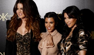 ** FILE ** Khloe Kardashian, left, Kourtney Kardashian, center, and Kim Kardashian arrive at the Kardashian Kollection launch party in Los Angeles, Wednesday, Aug. 17, 2011. The Kardashian Kollection designed by the Kardashian sisters is available at Sears. (AP Photo/Matt Sayles)