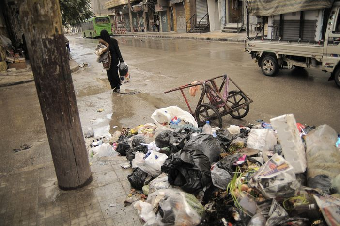 A women passes accumulated garbage in the Al-Bohout area of Aleppo, Syria, on Nov. 10, 2012. Due to heavy fighting and shelling, the garbage collection system collapsed weeks before. (Associated Press)