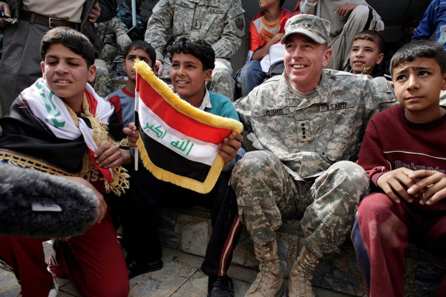 **FILE** Gen. David Petraeus, the top U.S. commander in Iraq, sits March 1, 2008, with Iraqi children during a youth soccer tournament in central Baghdad. (Associated Press)