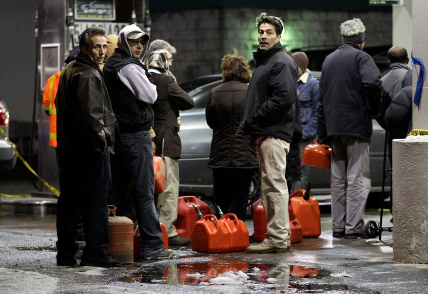 **FILE** People line up with containers as they wait in line to get gas at a Hess station in the Brooklyn borough of New York on Nov. 8, 2012. Fuel shortages and distribution delays that led to gas hoarding prompted New York City and Long Island to initiate an even-odd gas rationing plan. (Associated Press)