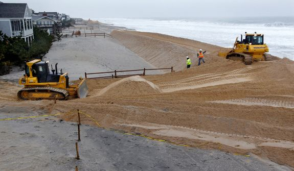 **FILE** Workers use heavy machinery spread sand in Harvey Cedars on Long Beach Island, N.J. A nor'easter smacked the storm-ravaged Jersey shore a week and half after Superstorm Sandy wrecked many of its beaches, dunes and boardwalks, and left low-lying communities newly vulnerable to flooding, wind damage and power outages. (Associated Press)