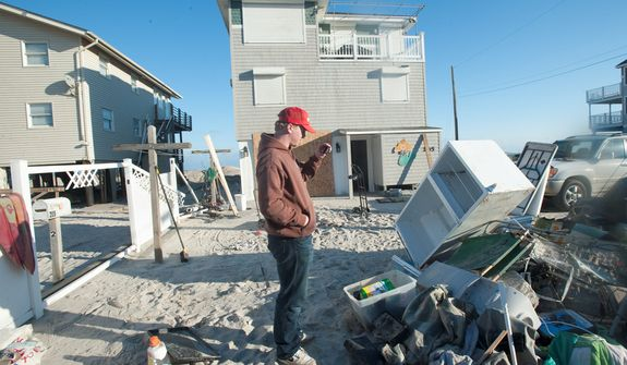 **FILE** Brian Meenan of Millwood, N.Y., takes photos and video of items that were destroyed by Superstorm Sandy in his family's beachfront house on 31st Street on Long Beach Island in Long Beach Township, N.J., on Nov. 5, 2012. (Associated Press)