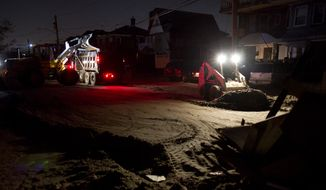 **FILE** A front loader works to remove sand and debris Nov. 11, 2012, as night falls on the Rockaway neighborhood in the Queens borough of New York in the wake of Superstorm Sandy. (Associated Press)