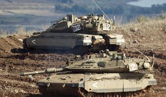 "** FILE ** Israeli tanks in the Israeli-controlled Golan Heights overlook the Syrian village of Bariqa on Nov. 12, 2012. The Israeli military says ""Syrian mobile artillery"" was hit after the Israelis responded to stray mortar fire from its northern neighbor. The incident marked the second straight day that Israel has responded to fire from Syria that does not appear to be aimed at Israeli targets; nonetheless, Israel has promised a tough response if the fire continues. (Associated Press)"