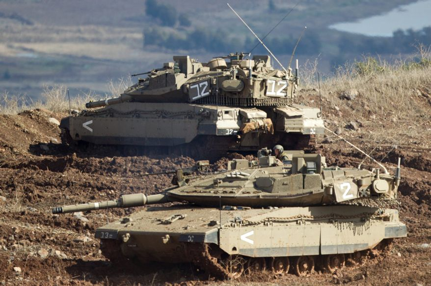 """** FILE ** Israeli tanks in the Israeli-controlled Golan Heights overlook the Syrian village of Bariqa on Nov. 12, 2012. The Israeli military says """"Syrian mobile artillery"""" was hit after the Israelis responded to stray mortar fire from its northern neighbor. The incident marked the second straight day that Israel has responded to fire from Syria that does not appear to be aimed at Israeli targets; nonetheless, Israel has promised a tough response if the fire continues. (Associated Press)"""