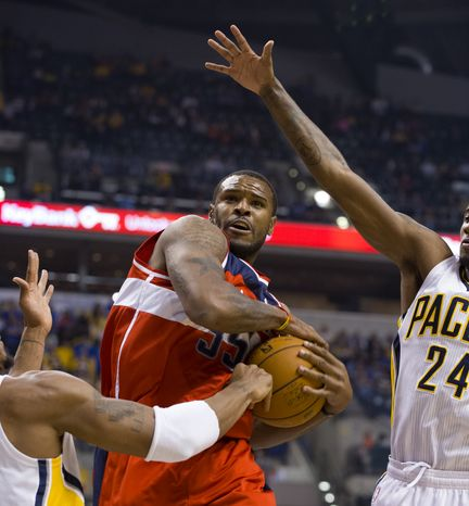 Washington Wizards power forward Trevor Booker (35) tries to maintain control of the ball as he drives the lane between Indiana Pacers David West, left, and Paul George (24) during first-half action in an NBA basketball game in Indianapolis, Saturday, Nov. 10, 2012.