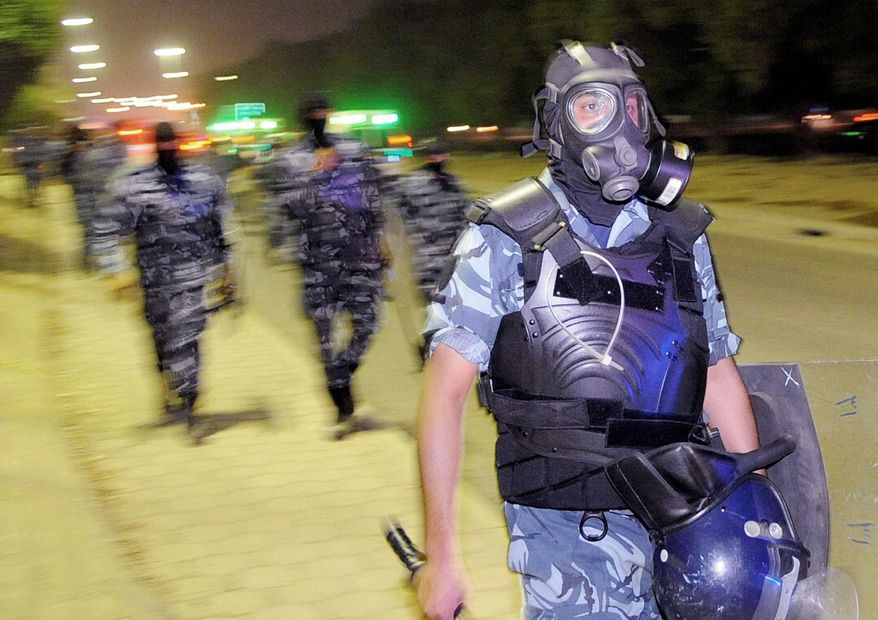 Riot police wield tear gas and stun grenades to disperse a throng of protesters in the Kuwait City suburb of Mishrefs. Strong-armed regimes in the oil-rich Persian Gulf have faced little resistance from Western governments that depend on the region as an energy supplier and as a military deterrent against Iran. (Associated Press)