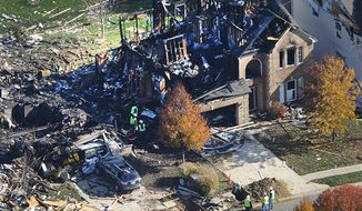 Citizens Energy workers continue their investigation Monday afternoon Nov. 12, 2012, by digging into the front sidewalk looking for possible explanation into the explosion of a house in Indianapolis. (AP Photo/WTHR Chopper 13/The Indianapolis Star, Matt Kryger)