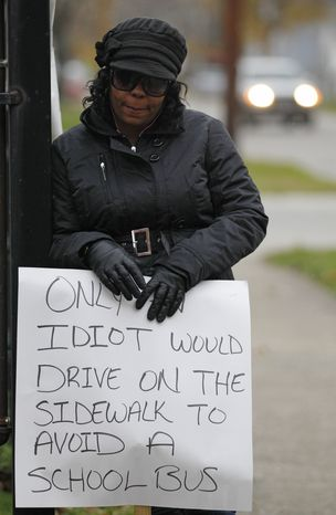 Shena Hardin holds up a sign in Cleveland on Nov. 13, 2012, to serve a highly public sentence for driving on a sidewalk to avoid a Cleveland school bus that was unloading children. (Associated Press)