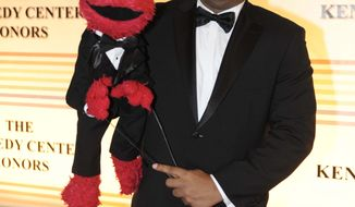 "FILE - In this Dec. 4, 2011 file photo, Elmo puppeteer Kevin Clash arrives with the ""Sesame Street"" muppet at the Kennedy Center for the Performing Arts for the Kennedy Center Honors gala performance in Washington. The man who accused Clash of having sex with him when he was a teen now says it isn't so. The man said in a statement released on Tuesday, Nov. 13, 2012 that his sexual relationship with Clash was adult and consensual. (AP Photo/Kevin Wolf, File)"