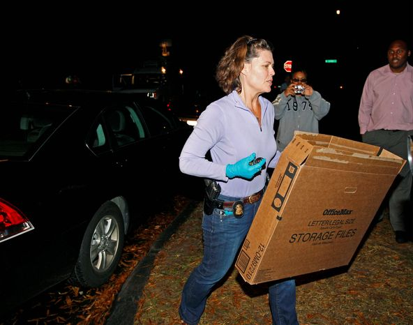 An FBI agent carries boxes to the home of Paula Broadwell, the woman whose affair with retired Gen. David Petraeus led to his resignation as CIA director, in the Dilworth neighborhood of Charlotte, N.C., on Nov. 13, 2012. (Associated Press)