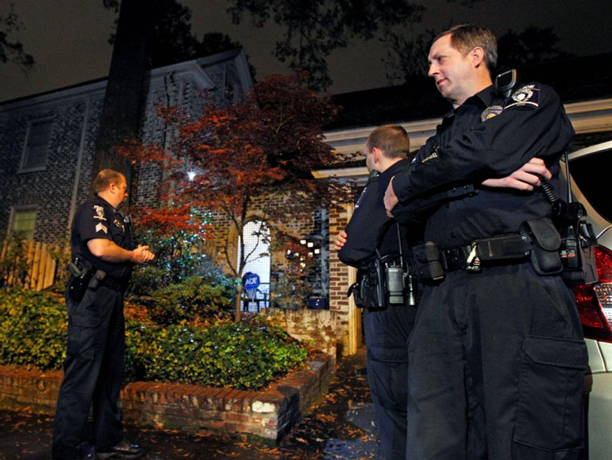 Charlotte-Mecklenburg police stand guard outside the home of Paula Broadwell, the woman whose affair with retired Gen. David Petraeus led to his resignation as CIA director, in the Dilworth neighborhood of Charlotte, N.C., on Nov. 13, 2012. (Associated Press)