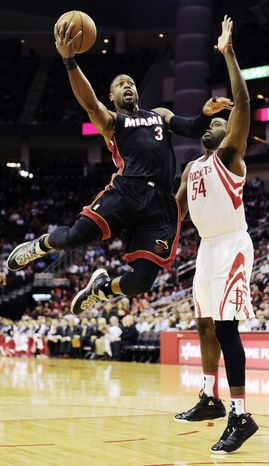 Miami Heat's Dwyane Wade (3) goes to the basket in front of Houston Rockets' Patrick Patterson (54) in the first half of an NBA