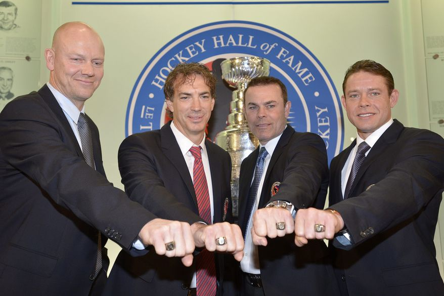 Hockey Hall of Fame inductees, from left, Mats Sundin, of Sweden, Joe Sakic, Adam Oates and Pavel Bure, of Russia,  pose for a photograph with their rings at the Hockey Hall of Fame in Toronto, Monday, Nov. 12, 2012. (AP Photo/The Canadian Press, Nathan Denette)