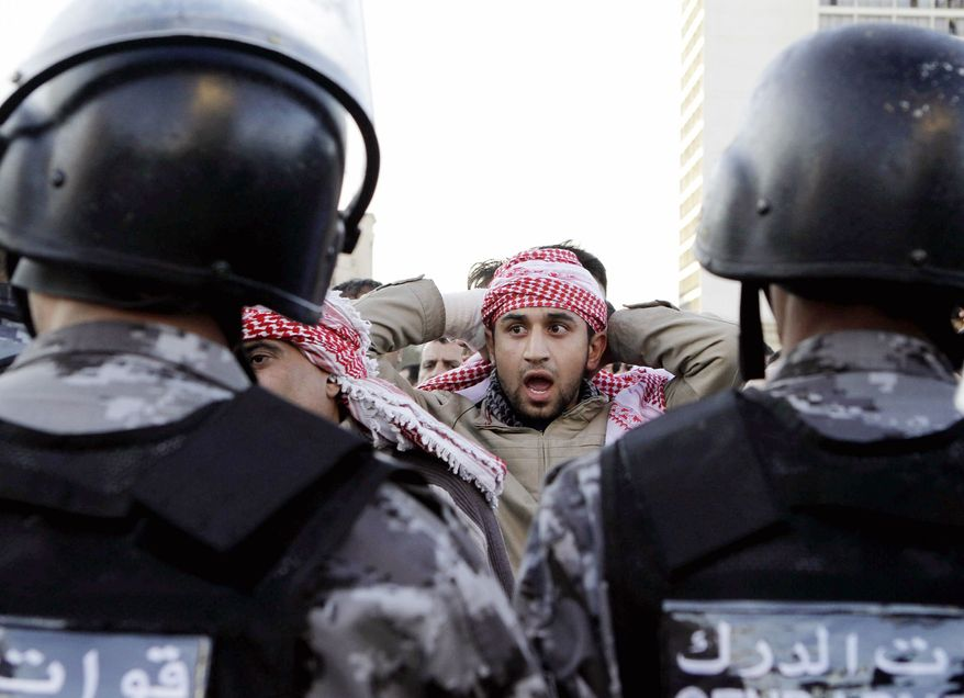 Jordanian policemen prepare to disperse protesters blocking a main road in Amman on Wednesday during a demonstration against the spike in fuel prices after the government lifted subsidies. Protesters denounced the king and threw rocks at police. (Associated Press)