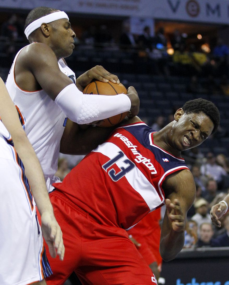 Charlotte Bobcats' Brendan Haywood, left, wrestles the ball from Washington Wizards' Kevin Seraphin, right, during the second half of an NBA basketball game in Charlotte, N.C., Tuesday, Nov. 13, 2012. Charlotte won 92-76. (AP Photo/Chuck Burton)