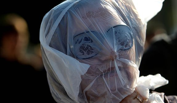 A protester covers her head in a plastic bag, meant to show that austerity measures are suffocating Greeks, outside Parliament during a union protest in Athens on Nov. 14, 2012. Workers across the European Union sought to present a united front against rampant unemployment and government spending cuts Wednesday with a string of strikes and demonstrations across the region. (Associated Press)