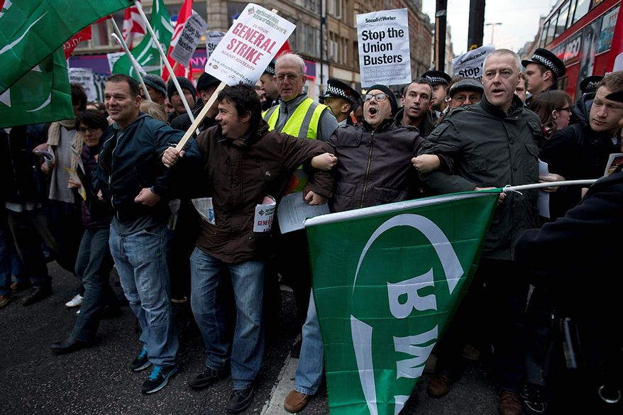 Protesters block traffic on one side of Oxford Street, London, whilst taking part in a picket and demonstration they said was over dismissals of 28 workers employed by contractors on the Crossrail transport project, for being trade union members, Wednesday, Nov. 14, 2012. The protest was held to coincide with planned European strikes on Wednesday in Spain, Italy, Greece, Portugal, France and Belgium against austerity measures and economic reforms.  Crossrail, due to start running services in 2018, is a new train line that will include twin-bore 21 km tunnels under central London and link 37 stations including transport hubs such as Heathrow airport with business districts including the City and Canary Wharf. (AP Photo/Matt Dunham)