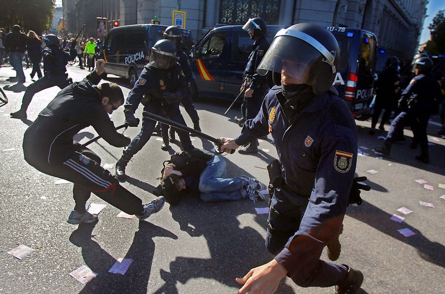 Police clash with protestors during a general strike in Madrid, Spain, Wednesday, Nov. 14, 2012. Spain's main trade unions stage a general strike, coinciding with similar work stoppages in Portugal and Greece, to protest government-imposed austerity measures and labor reforms. The strike is the second in Spain this year. (AP Photo/Andres Kudacki)