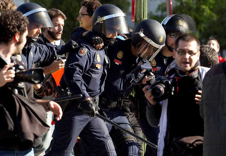 A police officer, center right, is helped by a colleague after getting hurt during a general strike in Madrid, Wednesday Nov. 14, 2012. A Spanish Interior Ministry official says 32 people have been arrested and 15 people treated for minor injuries in disturbances as a general strike in Spain against austerity measures and economic reforms began. The General Workers Union said the nationwide stoppage, the second this year, was being heeded by nearly 100 percent of workers Wednesday in the automobile, energy, shipbuilding and constructions industries. (AP Photo/Paul White)