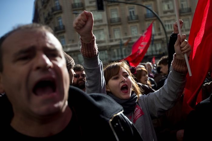 Demonstrators shout and wave flags as they march through Gran Via street during a general strike in Madrid, Spain, Wednesday, Nov. 14, 2012. Spain's General Workers' Union said the nationwide stoppage, the second this year, was being observed by nearly all workers in the automobile, energy, shipbuilding and constructions industries. (AP Photo/Daniel Ochoa de Olza)