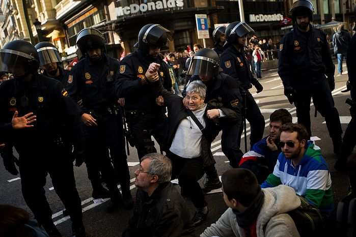 A protestor is held by riot police during clashes in a general strike in Madrid, Spain, Wednesday, Nov. 14, 2012. Spain's General Workers' Union said the nationwide stoppage, the second this year, was being observed by nearly all workers in the automobile, energy, shipbuilding and constructions industries. (AP Photo/Daniel Ochoa de Olza)