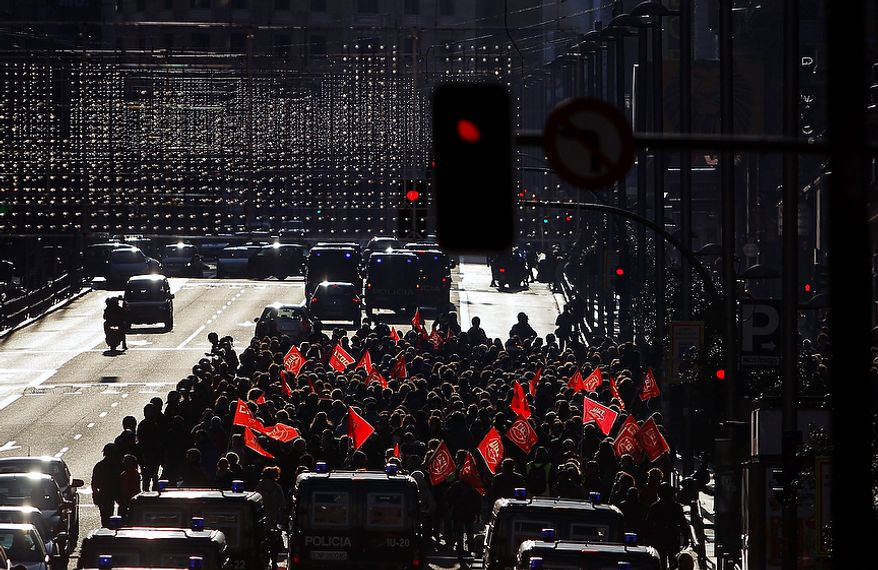 Protestors march during a general strike in Madrid, Spain, Wednesday, Nov. 14, 2012. Spain's main trade unions staged a general strike, coinciding with similar work stoppages in Portugal and Greece, to protest government-imposed austerity measures and labor reforms. The strike is the second in Spain this year. (AP Photo/Andres Kudacki)