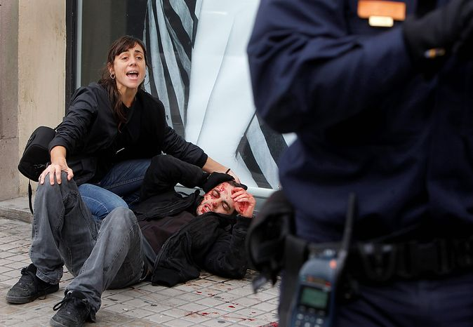 A woman cries out as she tries to help a protestor who lies injured on the ground as a policeman stands nearby, after clashes with riot police during a general strike in Valencia, Spain, Wednesday, Nov. 14, 2012.  Spain's General Workers' Union said the nationwide stoppage, the second this year, was being observed by nearly all workers in the automobile, energy, shipbuilding and constructions industries. (AP Photo/Fernando Hernandez)