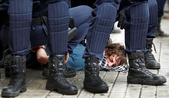 Riot police apprehend a protestor during a general strike in Valencia, Spain, Wednesday, Nov. 14, 2012. Spain's main trade unions stage a general strike, coinciding with similar work stoppages in Portugal and Greece, to protest government-imposed austerity measures and labor reforms. The strike is the second in Spain this year. (AP Photo/ Fernando Hernandez)