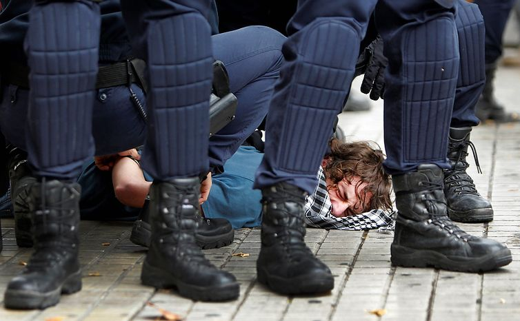 Riot police apprehend a protestor during a general strike in Valencia, Spain, Wednesday, Nov. 14, 2012. Spain's main trade unions stage a general strike, coinciding with similar work stoppages in Portugal and Greece, to protest government-impo