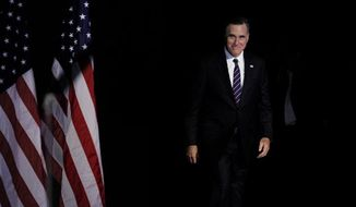 **FILE** Republican presidential candidate Mitt Romney emerges Nov. 7, 2012, from backstage to concede his quest for President of the United States at his election night event at the Boston Convention Center in Boston. (Associated Press)