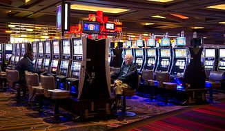 People play slot machines at Maryland Live! Casino in Hanover, Md. on Wednesday, Nov. 14, 2012. The casino held a press conference Wednesday to announce that it plans to add live game tables and 24-hour gambling as soon as possible after the state issues the necessary governing regulations. They hope to have the 150 new table games in place by spring. (Barbara L. Salisbury/The Washington Times)