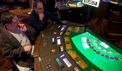 "Merle Miller, left, of Clinton, Md. and Pablo (who did not give his last name) of Silver Spring, Md. play an electronic table version of Black Jack at Maryland Live! Casino in Hanover, Md. on Wednesday, Nov. 14, 2012. The casino announced today in a press conference that it will be adding live table games, so many of these electronic versions will be replaced, hopefully by spring. ""You just hope you get a good dealer who gets into it,"" says Miller, who says he plays Black Jack everywhere and is excited about the prospect of playing with a live dealer. ""It's fun,"" he says. (Barbara L. Salisbury/The Washington Times)"