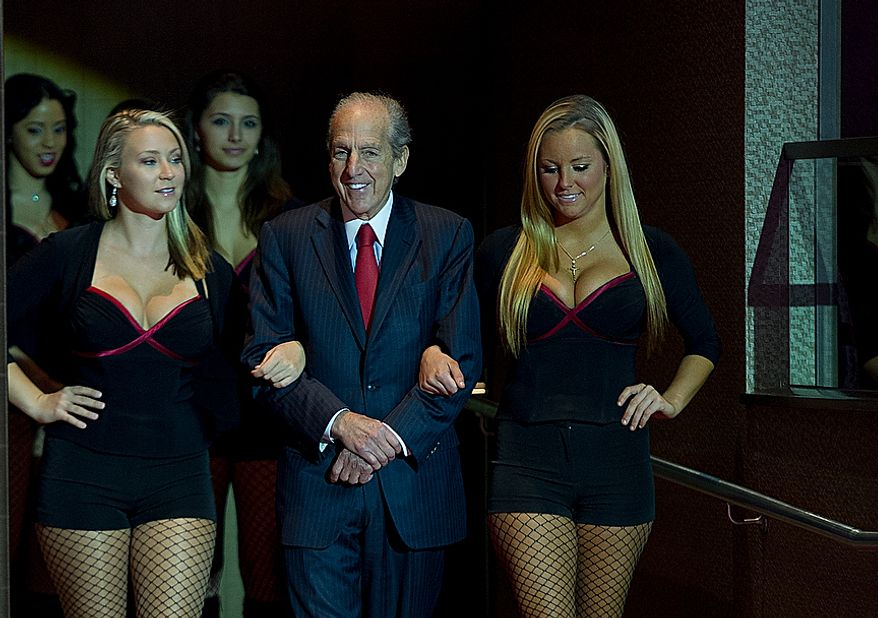 David Cordish with The Cordish Company is escorted to the microphone by women who work at Maryland Live! Casino to announce plans for the casino at Arundel Mills Mall in Hanover, Md. to add live table games and 24-hour gambling at a press conference Wednesday, Nov. 14, 2012. Approximately 150 table games will be added to the casino floor, including Black Jack, Roulette, Craps, Sic Bo and Baccarat. The casino is prepared to immediately start the modifications necessary to bring in the new games, with the hope that they will be in place by the spring. (Barbara L. Salisbury/The Washington Times)