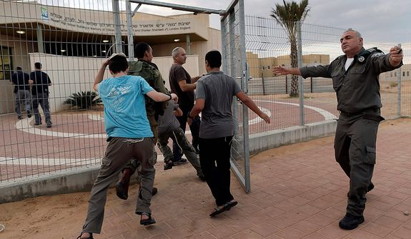 Israeli soldiers and civilians run to a rocket shelter as a siren sounds signaling an attack coming from the nearby Gaza Strip in Neva settlement, near the Israel-Egypt border, Wednesday, Nov. 14, 2012. (AP Photo/Tsafrir Abayov)
