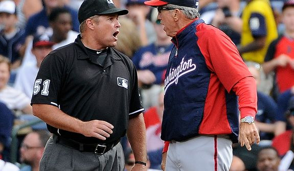**FILE** Washington Nationals manager Davey Johnson (right) argues with first base umpire Marvin Hudson before being ejected during the sixth inning of the Nationals' 5-4 road loss to the Atlanta Braves on Sept. 15, 2012. (Associated Press)