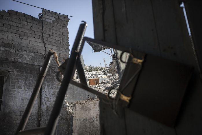 A street of destroyed buildings is reflected Nov. 13, 2012, in a mirror used by rebel fighters to keep an eye on a Syrian army position in Aleppo, Syri