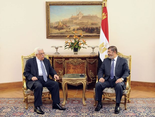 In this photo, released by the Egyptian Presidency, Palestinian President Mahmoud Abbas, left, meets with Egyptian President Mohammed Morsi, right, in Cairo, Egypt, Tuesday, Nov. 13, 2012. (AP Photo/Egyptian Pr
