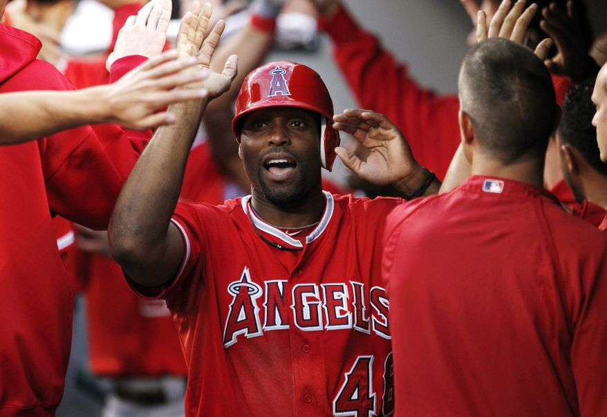 FILE - This Aug. 31, 2012 file photo shows Los Angeles Angels' Torii Hunter being congratulaed in the dugout during a baseball game against the Seattle Mariners in Seattle. A person with knowledge of the negotiations says free agent outfielder Hunter has agreed to a two-year deal with the Detroit Tigers. The person, who spoke Wednesday, Nov. 14, 2012, on condition of anonymity because no announcement has been made, says the deal is pending a physical. (AP Photo/Elaine Thompson, File)
