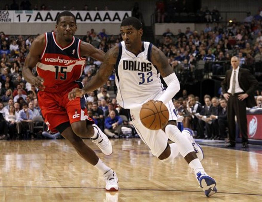 Dallas Mavericks' O.J. Mayo (32) gets by Washington Wizards' Jordan Crawford (15) on a charge to the basket in the second half of an NBA game, Wednesday, Nov. 14, 2012, in Dallas. Mayo led all scoring with 25 points in the 107-101 Mavericks win. (AP Photo/Tony Gutierrez)