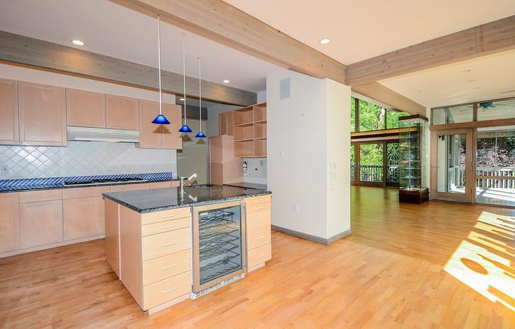 The kitchen features wood cabinetry, an oversized refrigerator and a granite-topped center island with blue pendant lights hanging over it.