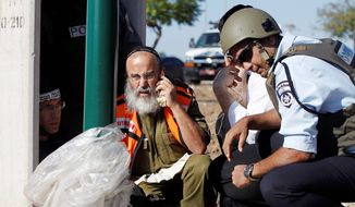 Israeli security personnel take cover in Kiryat Malachi on Thursday after three Israelis were killed in a rocket attack from the Gaza Strip. The escalation in warfare on both sides threatens to deepen a bruising Israeli air, naval and artillery offensive against Palestinian rocket squads. (Associated Press)