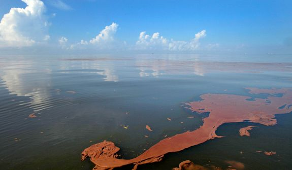 ** FILE ** Oil from the BP Deepwater Horizon spill floats on the water with clouds reflected in the sheen on Barataria Bay off the coast of Louisiana, June 10, 2010. (AP Photo/Charlie Riedel)